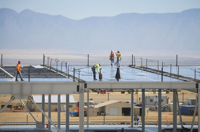 FILE - In this Nov. 14, 2017, file photo, construction workers build one of the Facebook data center buildings in Los Lunas, N.M. A powerful regulatory authority in New Mexico decided Tuesday, April 16, 2019, it is requiring the state's largest utility to bill Facebook $39 million for the construction of a new transmission line, a move that the social media giant says could affect its long-term operations in the state. (Marla Brose/The Albuquerque Journal via AP, File)