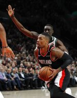 Portland Trail Blazers guard Damian Lillard, left, drives to the basket as Milwaukee Bucks guard Tony Snell defends during the first half of an NBA basketball game in Portland, Ore., Tuesday, Nov. 6, 2018. (AP Photo/Steve Dipaola)