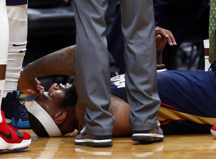 FILE - In this Jan. 26, 2018, file photo, then-New Orleans Pelicans center DeMarcus Cousins lies on the court while being tended to after an injury during the second half of an NBA basketball game against the Houston Rockets in New Orleans. A person with knowledge of the situation says Los Angeles Lakers center DeMarcus Cousins is undergoing tests to confirm a preliminary diagnosis of a ligament tear in his knee. Cousins was injured in a workout in Las Vegas this week, according to the person who spoke on condition of anonymity to The Associated Press on Thursday, Aug. 15, 2019, because no official diagnosis has been released publicly. (AP Photo/Gerald Herbert, File)