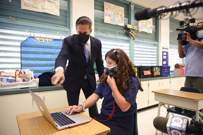 FILE- In this Aug. 31, 2020 file photo, Miami-Dade County Public Schools' superintendent Alberto Carvalho glances towards student Emily Acosta as she does school work in her mother's class as he stopped by Bob Graham Education Center in Miami Lakes, Fla. Authorities announced, Thursday, Sept. 3, 2020, that a 16-year-old student has been arrested for orchestrating a series of network outages and cyberattacks during the first week of school in Florida's largest district. (Carl Juste/Miami Herald via AP, File)