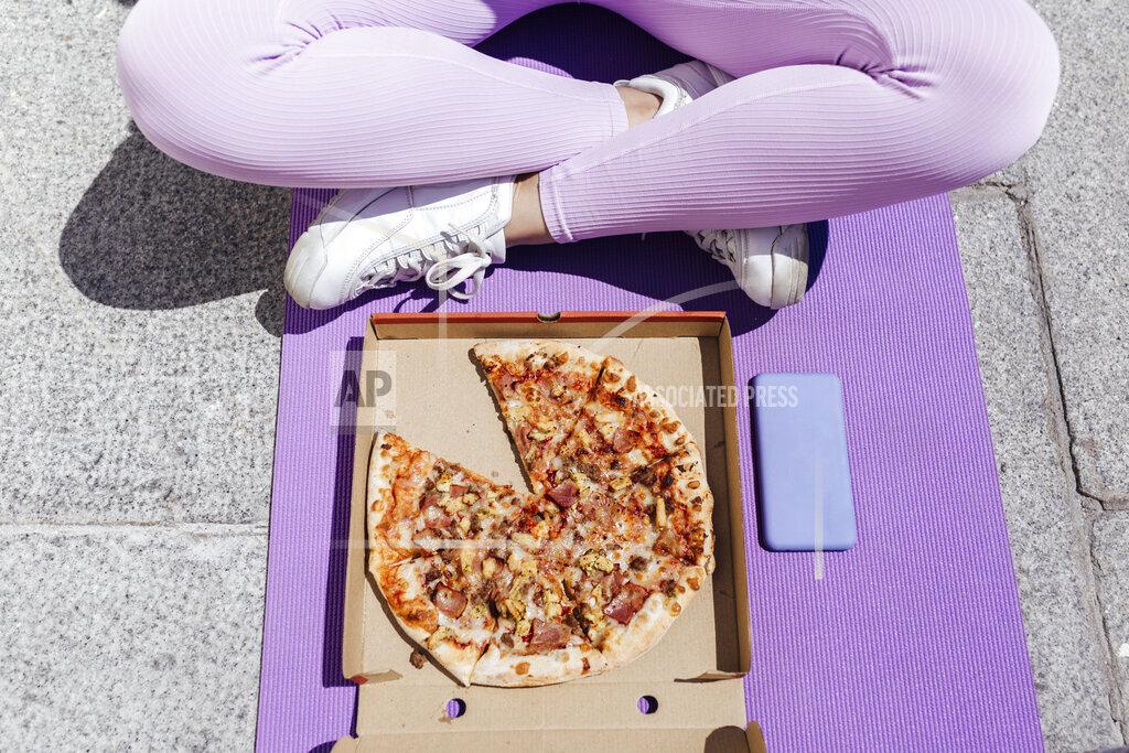Female athlete sitting cross-legged in front of pizza on exercise mat