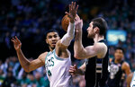 Boston Celtics forward Jayson Tatum, left, pressures Milwaukee Bucks center Tyler Zeller, right, during the first quarter of Game 2 of an NBA basketball first-round playoff series in Boston, Tuesday, April 17, 2018. (AP Photo/Charles Krupa)