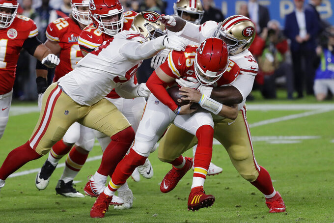 Kansas City Chiefs quarterback Patrick Mahomes (15) runs against San Francisco 49ers' DeForest Buckner, left, and Earl Mitchell during the first half of the NFL Super Bowl 54 football game Sunday, Feb. 2, 2020, in Miami Gardens, Fla. (AP Photo/Seth Wenig)