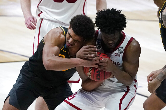 Missouri guard Mark Smith, left, fights for a loose ball with Oklahoma guard Elijah Harkless, right, during the second half of a first-round game in the NCAA men's college basketball tournament at Lucas Oil Stadium, Saturday, March 20, 2021, in Indianapolis. (AP Photo/Darron Cummings)