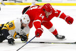 Pittsburgh Penguins defenseman Marcus Pettersson (28) and Detroit Red Wings center Robby Fabbri (14) battle for the puck in the second period of an NHL hockey game Friday, Jan. 17, 2020, in Detroit. (AP Photo/Paul Sancya)