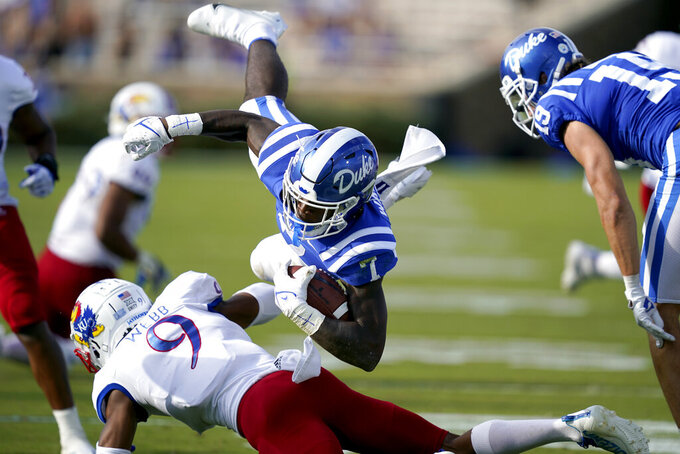 Duke running back Jordan Waters (7) is hit by Kansas cornerback Jeremy Webb (9) during the first half of an NCAA college football game in Durham, N.C., Saturday, Sept. 25, 2021. (AP Photo/Gerry Broome)