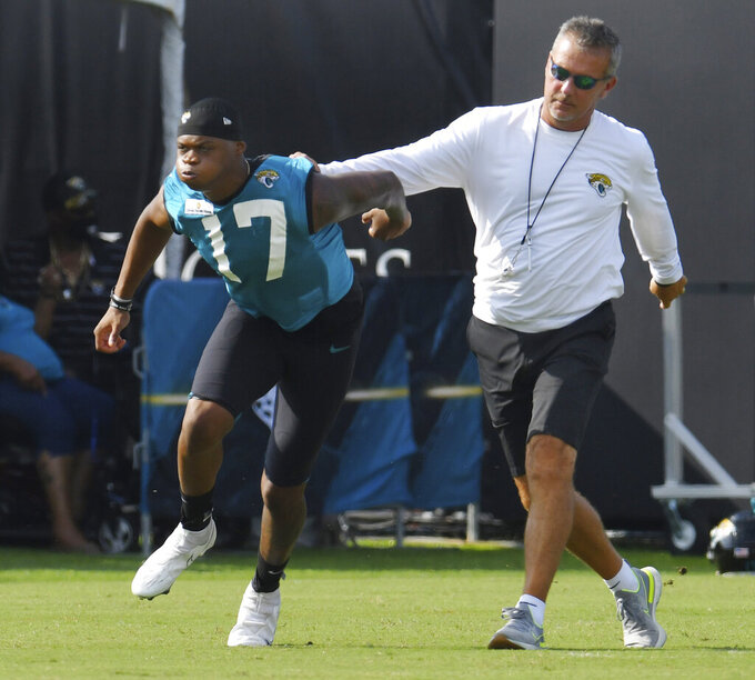 Jacksonville Jaguars head coach Urban Meyer holds wide receiver DJ Chark Jr. by the jersey as he works with him at the start of the team's NFL football practice in Jacksonville, Fla., Friday, July 30, 2021. (Bob Self/The Florida Times-Union via AP)