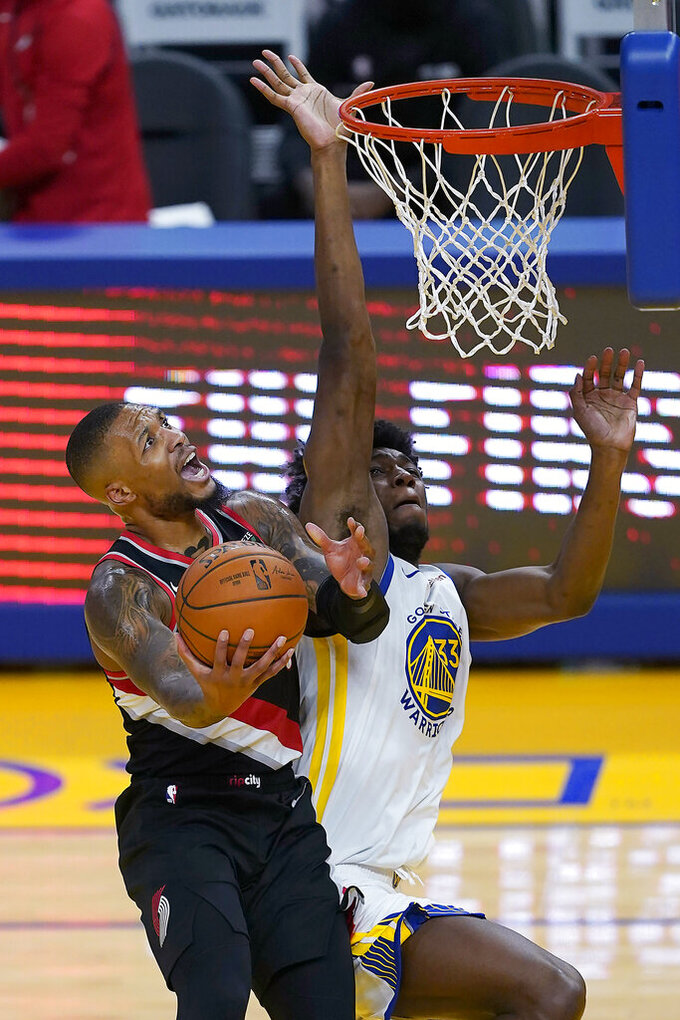 Portland Trail Blazers guard Damian Lillard (0) drives to the basket against Golden State Warriors center James Wiseman (33) during the first half of an NBA basketball game in San Francisco, Friday, Jan. 1, 2021. (AP Photo/Tony Avelar)