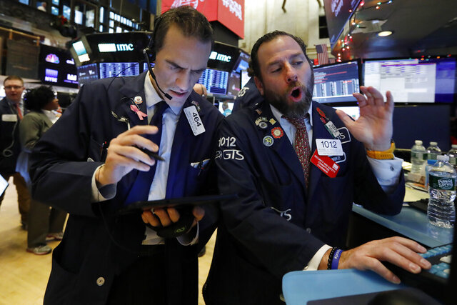 FILE - In this Dec. 5, 2019, file photo, trader Gregory Rowe, left, and specialist Michael Pistillo work on the floor of the New York Stock Exchange. The U.S. stock market opens at 9:30 a.m. EST on Thursday, Dec. 12. (AP Photo/Richard Drew, File)