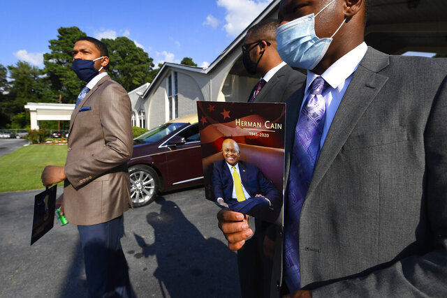 Attendees leave a public viewing for Herman Cain, Thursday, Aug. 6, 2020 in Atlanta. The former Republican presidential candidate, radio host, and entrepreneur died on July 30, after being hospitalized with COVID-19 and will be laid to rest this week. He was 74. (AP Photo/John Amis)