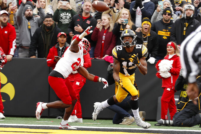 Iowa wide receiver Brandon Smith (12) catches a 15-yard touchdown pass in front of Nebraska defensive back Dicaprio Bootle, left, during the first half of an NCAA college football game, Friday, Nov. 23, 2018, in Iowa City, Iowa. (AP Photo/Charlie Neibergall)