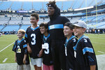 Carolina Panthers quarterback Cam Newton poses with children before the first half an NFL preseason football game against the Buffalo Bills, Friday, Aug. 16, 2019, in Charlotte. (AP Photo/Brian Blanco)