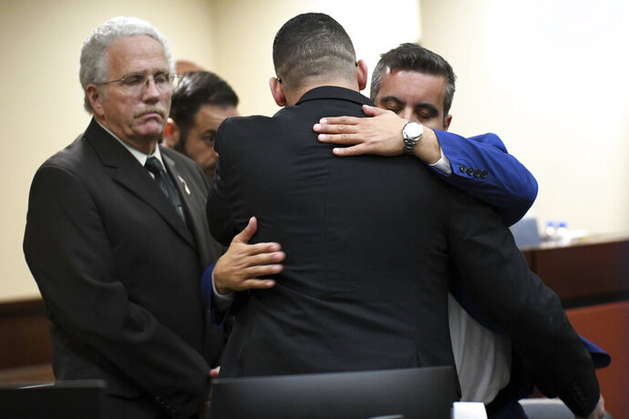 Sigfredo Garcia hugs his defense attorney Mauricio Padilla on Friday, Oct. 11, 2019, in Tallahassee, Fla., after learning the jury found him guilty for the 2014 murder of Dan Markel. (Alicia Devine/Tallahassee Democrat via AP)