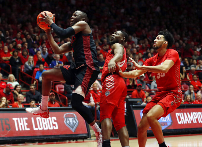 San Diego State guard Adam Seiko, left, goes up for a layup against New Mexico forward Jordan Arroyo, right, and guard Zane Martin during the first half of an NCAA college basketball game on Wednesday, Jan. 29, 2020 in Albuquerque, N.M. (AP Photo/Andres Leighton)