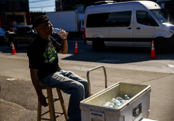 Carl Goodwin, manager of Seattle Sausage, takes a water break while selling bottles of water to baseball fans leaving the Mariners game on a warm Wednesday afternoon, June 23, 2021, in the SoDo neighborhood of Seattle. Forecasts say extreme heat will roast the Puget Sound region from Saturday through Monday. (Amanda Snyder/The Seattle Times via AP)