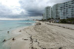 The beach is empty where a few tourists spend time on the waters' edge in Cancun, Mexico, Saturday, June 13, 2020. An irony of the coronavirus pandemic is that the idyllic beach vacation in Mexico in the brochures really does exist now: the white sand beaches are sparkling clean and empty on the Caribbean coast. (AP Photo/Victor Ruiz)