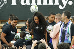 Pop singer Ciara, center, the wife of Seattle Seahawks NFL football quarterback Russell Wilson, left, heads a soccer ball, Monday, Aug. 19, 2019, during an event in Seattle held to introduce the couple, hip-hop artist Macklemore, and others as new members of the Seattle Sounders MLS soccer team's ownership group. (AP Photo/Ted S. Warren)