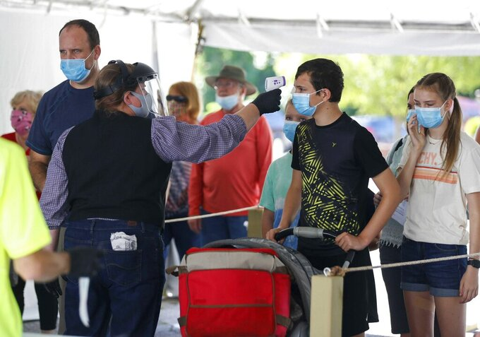 FILE - In this June 13, 2021, file photo, a Silver Dollar City employee takes the temperature of guests before they are allowed to enter the park just west of Branson, Mo. Across the U.S., the seven-day rolling average for daily new cases in the U.S. rose over the past two weeks  on Tuesday, July 21.  (Nathan Papes/The Springfield News-Leader via AP)
