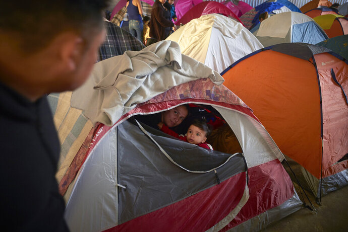 In this March 5, 2019, image, Ruth Aracely Monroy, center, looks out of the family's tent alongside her 10-month-old son, Joshua, as her husband, Juan Carlos Perla, left, passes inside a shelter for migrants in Tijuana, Mexico. After fleeing violence in El Salvador and requesting asylum in the United States, the family was returned to Tijuana to await their hearing in San Diego. They were one of the first families to contend with a new policy that makes asylum seekers stay in Mexico while their cases wind through U.S. immigration courts. (AP Photo/Gregory Bull)