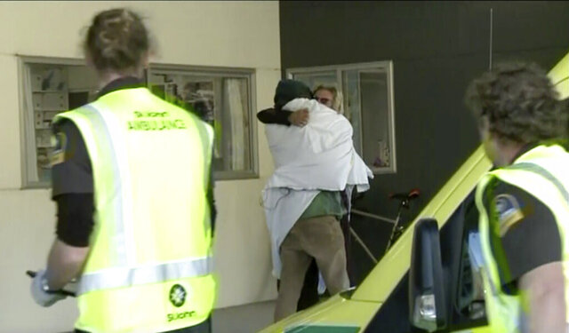 In this image made from May 27, 2020, video, one of the two hikers found alive is wrapped in a white blanket hugs another person as they enter a hospital in Nelson, New Zealand. Two hikers rescued in the New Zealand wilderness Wednesday got lost in fog and exhausted their food but survived 19 days with only minor injuries, police said. (Newshub/TVNZ via AP)