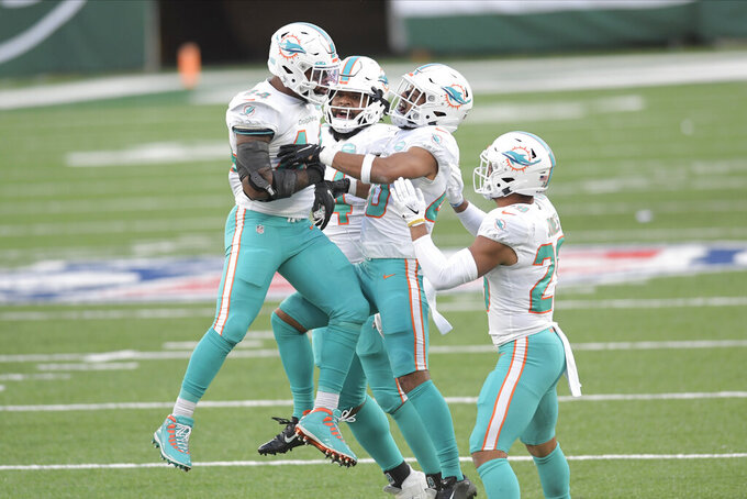Miami Dolphins' Elandon Roberts, left, celebrates a stop with teammates during the second half of an NFL football game against the New York Jets, Sunday, Nov. 29, 2020, in East Rutherford, N.J. (AP Photo/Bill Kostroun)