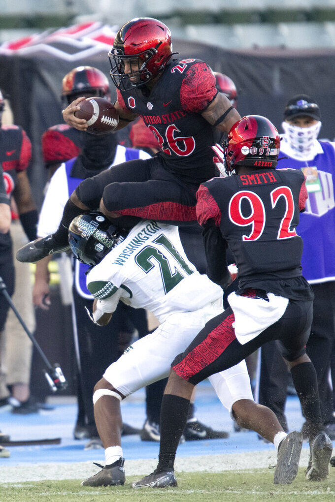 San Diego State running back Kaegun Williams, top, tries to leap over Hawaii defensive back Michael Washington during the second half of an NCAA college football game Saturday, Nov. 14, 2020, in Carson, Calif. (AP Photo/Kyusung Gong)