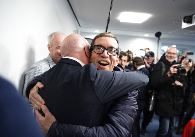 German Jens Soering, center, is embraced by man after his arrival at the Frankfurt Airport in Frankfurt, Germany, Tuesday, Dec. 17, 2019. The son of a German diplomat, who served more than 33 years in prison for a murder in Virginia he has steadfastly maintained he did not commit, arrived in Frankfurt Tuesday after being released on parole. (Andreas Arnold/dpa via AP)