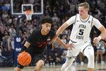San Diego State guard Trey Pulliam (4) is defended by Utah State guard Sam Merrill during the first half of an NCAA college basketball game Saturday, Jan. 4, 2020, in Logan, Utah. (AP Photo/Eli Lucero)