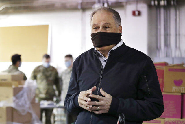 Gov. Jay Inslee wears a makeshift mask as he speaks with media members while visiting inside Nourish Pierce County warehouse, where Washington National Guard members were packing food in response to the coronavirus outbreak Friday, April 3, 2020, in Lakewood, Wash. National Guard members will be packing food at the warehouse five days a week for delivery to 26 food banks, taking over for volunteers who normally pack over 300 boxes a day. The need for food at the pantries in the area is expected to at least double in the coming weeks. (AP Photo/Elaine Thompson)
