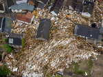 Debris of houses and trees surround houses in Schuld, Germany, Friday, July 16, 2021. Two days before the Ahr river went over the banks after strong rain falls causing severals deaths and hundreds of people missing. (AP Photo/Michael Probst)