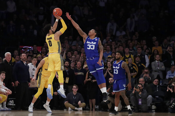 Marquette guard Markus Howard (0) attempts a shot against Seton Hall guard Shavar Reynolds (33) during the second half of an NCAA college basketball semifinal game in the Big East men's tournament, early Saturday, March 16, 2019, in New York. Seton Hall won 81-79. (AP Photo/Julio Cortez)
