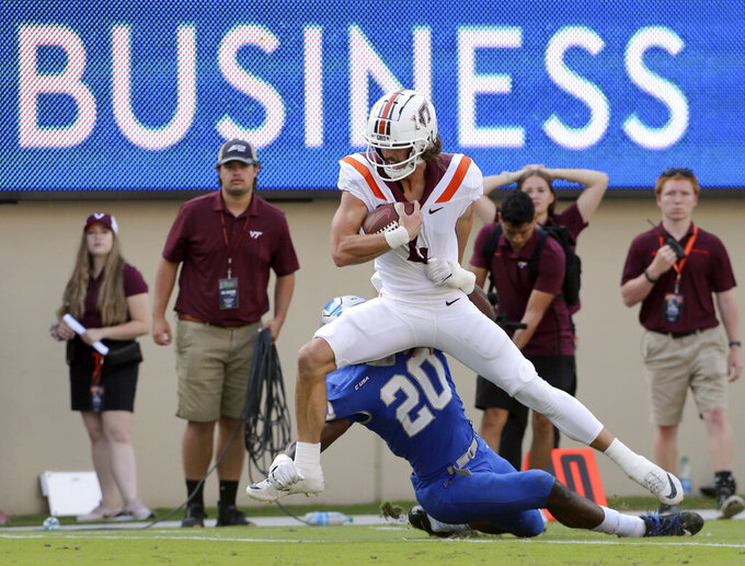 Virginia Tech quarterback Connor Blumrick (4) runs for a first down past Middle Tennessee linebacker DQ Thomas (20) in the second half of an NCAA college football game, Saturday, Sept. 11, 2021, in Blacksburg Va. (AP Photo/Matt Gentry)