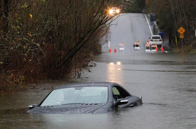 A driver drove past road closed signs on Southeast Seventh Place in Bellevue, Wash., near the Lake Hills Connector, which was covered with about four feet of water, and was able to swim to safety when the car stalled, Friday, Dec. 20, 2019. A storm that has brought record rainfall to the Northwest has broken some records, prompted flood warnings, disrupted train traffic and caused some power outages. (Ellen M. Banner/The Seattle Times via AP)