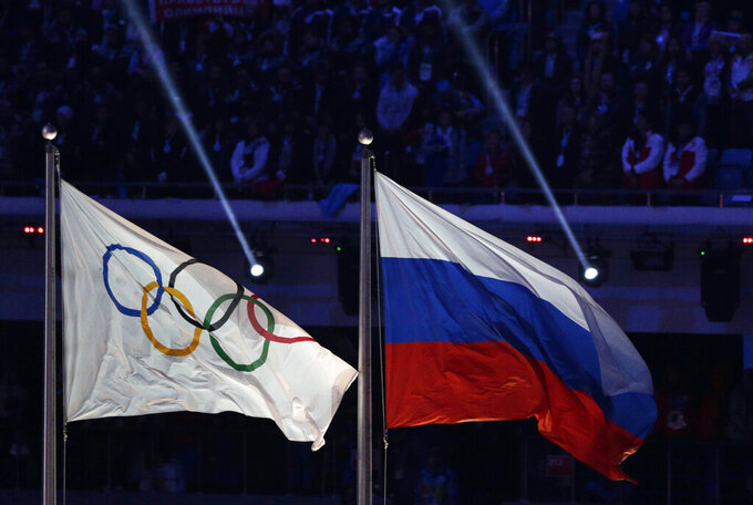 FILE - In this Feb. 23, 2014 file photo, the Russian national flag, right, flies after next to the Olympic flag during the closing ceremony of the 2014 Winter Olympics in Sochi, Russia. The World Anti-Doping Agency banned Russia on Monday Dec. 9, 2019 from the Olympics and other major sporting events for four years, though many athletes will likely be allowed to compete as neutral athletes. (AP Photo/Matthias Schrader, File)