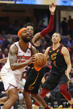 New York Knicks' Marcus Morris Sr., left, drives against the Cleveland Cavaliers in the second half of an NBA basketball game, Monday, Jan. 20, 2020, in Cleveland. New York won 106-86. (AP Photo/Tony Dejak)