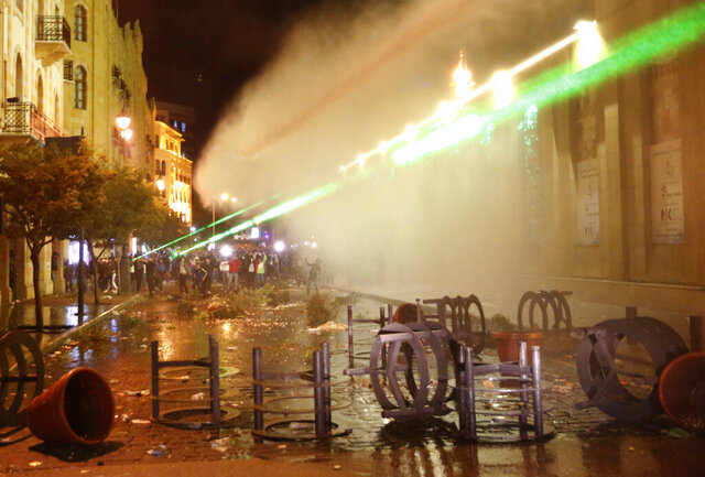 Anti-government protesters use their Laser ray lights, as they are sprayed by water from the riot police during a protest near the parliament square, in downtown Beirut, Lebanon, Sunday, Dec. 15, 2019. Lebanese security forces fired tear gas, rubber bullets and water cannons Sunday to disperse hundreds of protesters for a second straight day, ending what started as a peaceful rally in defiance of the toughest crackdown on anti-government demonstrations in two months. (AP Photo/Hussein Malla)