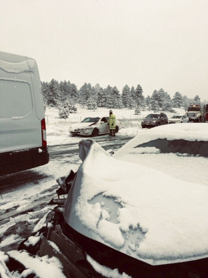 This photo provided by the Ponderosa Fire District shows a multiple car accident caused by slick roads from a snow fall near Flagstaff, Ariz. on Thursday, May 23, 2019. Northern Arizona is getting a rare dose of late-season snow. The National Weather Service is recording snow in the inches near Flagstaff, in Seligman and at the Grand Canyon's South Rim. (Erin Hudman/Ponderosa Fire District via AP)