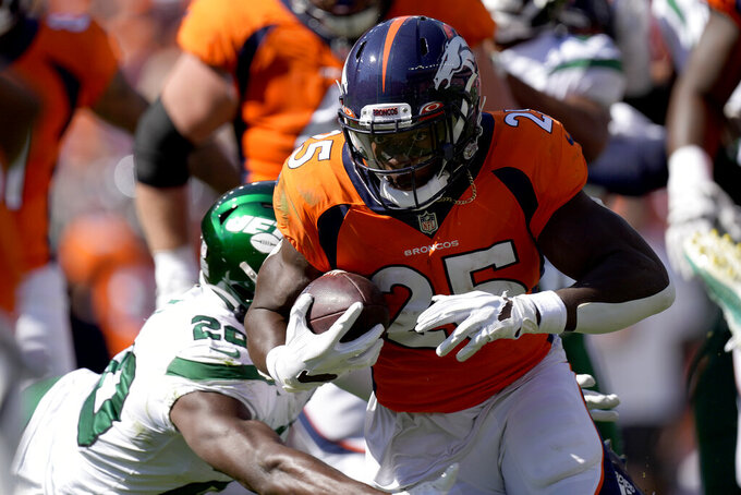 Denver Broncos running back Melvin Gordon (25) runs as New York Jets free safety Marcus Maye (20) makes the tackle during the first half of an NFL football game, Sunday, Sept. 26, 2021, in Denver. (AP Photo/David Zalubowski)