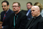 From front to back, Samuel Aquila, archbishop of the Denver diocese of the Roman Catholic Church, Very Rev. Randy Dollins, vicar general, and Colorado Attorney General Phil Weiser listen about the plan to have a former federal prosecutor review the sexual abuse files of Colorado's Roman Catholic dioceses at a news conference Tuesday, Feb. 19, 2019, in Denver. The church will pay reparations to victims under a voluntary joint effort with the state attorney general. (AP Photo/David Zalubowski)