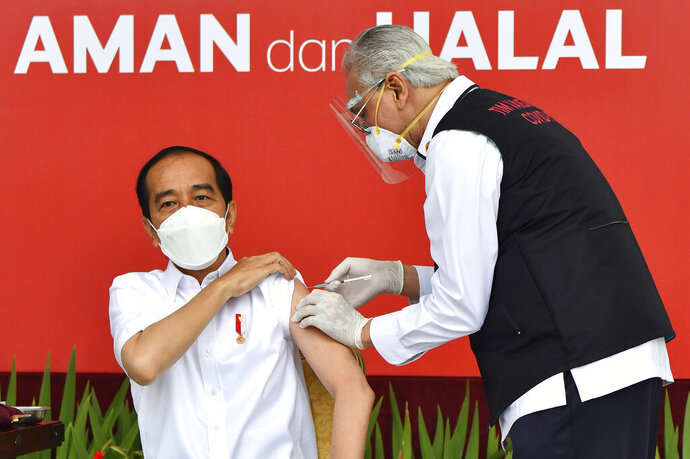 In this photo released by Indonesian Presidential Palace, President Joko Widodo, left, receives a shot of COVID-19 vaccine at Merdeka Palace in Jakarta, Indonesia, Wednesday, Jan. 13, 2021. Widodo on Wednesday received the first shot of a Chinese-made COVID-19 vaccine after Indonesia approved it for emergency use and began efforts to vaccine millions of people in the world's fourth most populated country. Writings on the banner in the background read