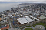 In this March 26, 2020, photo, KeyArena is shown as viewed from the Space Needle in Seattle with renovation construction temporarily halted due to the outbreak of the coronavirus. The pandemic has created questions of scheduling and worker health as eight stadiums or arenas are under construction or about to break ground in the five major professional sports leagues in North America. Construction on the home of the WNBA Seattle Storm and Seattle's expansion NHL team — which is scheduled to begin play in the 2021-22 season — was allowed to resume a few days later with an urgency associated with the roof, which weighs more than 40 million pounds and is currently resting mostly on temporary supports. (AP Photo/Ted S. Warren)