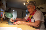 """Mae Krier, 95, of Levittown, Pa., an original """"Rosie the Riveter,"""" demonstrates the process of working on making one of her polka dotted masks at her home in Levittown, Pa., on Wednesday, July 28, 2021. Krier spent her time building airplanes for Boeing during World War II which earned her the title of Rosie the Riveter. She spent years getting other Rosies recognized.""""It is important for women to go after what they want or like because they are just as capable as a man,"""" Krier said. (Tyger Williams/The Philadelphia Inquirer via AP)"""