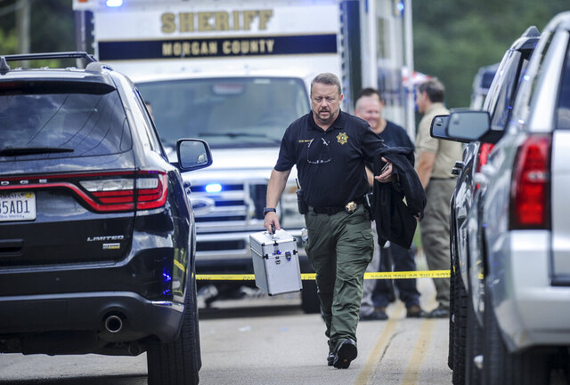 A Morgan County, Ala. investigator works at the scene, Friday, June 5, 2020, in Valhermoso Springs, Ala., where numerous people were found fatally shot. Deputies responding to a call about a shooting in Alabama found seven people dead inside a home that had been set afire early Friday, authorities said. (Jeronimo Nisa/The Decatur Daily via AP)