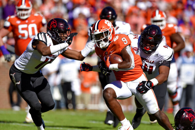 Clemson's Travis Etienne rushes through Louisville's Dee Smith (11) and G.G. Robinson to score a touchdown during the first half of an NCAA college football game Saturday, Nov. 3, 2018, in Clemson, S.C. (AP Photo/Richard Shiro)