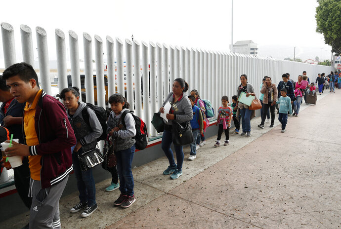 FILE - This July 26, 2018, file photo shows people lining up to cross into the United States to begin the process of applying for asylum near the San Ysidro port of entry in Tijuana, Mexico. A court-appointed committee has yet to find the parents of 628 children separated at the border early in the Trump administration. (AP Photo/Gregory Bull, File)