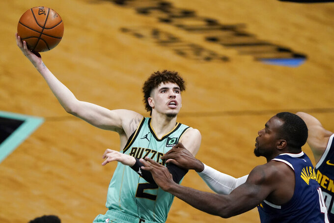 FILE - In this May 11, 2011, file photo, Charlotte Hornets guard LaMelo Ball, left, shoots over Denver Nuggets forward Paul Millsap during the second half of an NBA basketball game in Charlotte, N.C. Ball won the ESPY as best breakthrough athlete, Saturday, July 11. (AP Photo/Chris Carlson, File)