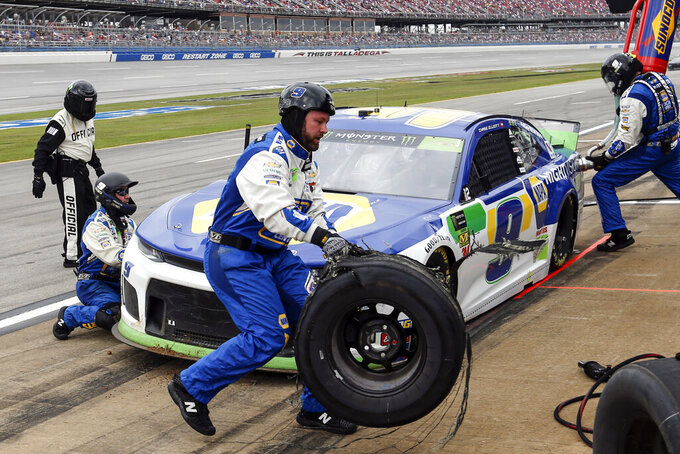 A crew member for Chase Elliott (9) carries a blown tire back to the wall during a NASCAR Cup Series auto race at Talladega Superspeedway, Monday, Oct 14, 2019, in Talladega, Ala. (AP Photo/Butch Dill)