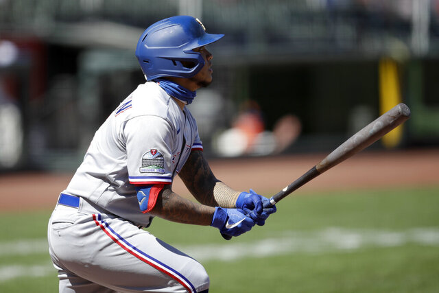 Texas Rangers' Willie Calhoun swings for an RBI sacrifice fly against the San Francisco Giants during the seventh inning of a baseball game Sunday, Aug. 2, 2020, in San Francisco. (AP Photo/Ben Margot)