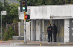 El Monte Police Chief David Reynoso, left, with another officer stand outside the First Works Baptist Church tagged with graffiti, after an explosion in El Monte, Calif., Saturday, Jan. 23, 2021. The FBI and local police are investigating the explosion early Saturday at the Los Angeles-area church that had been the target of protests for its anti-LGTBQ message. (AP Photo/Damian Dovarganes)