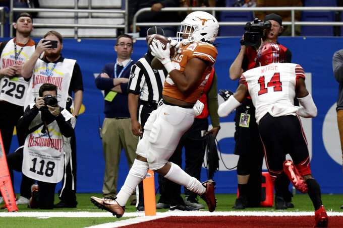 Texas running back Keaontay Ingram (26) catches a touchdown pass next to Utah defensive back Josh Nurse (14) during the second half of the Alamo Bowl NCAA college football game in San Antonio, Tuesday, Dec. 31, 2019. (AP Photo/Eric Gay)